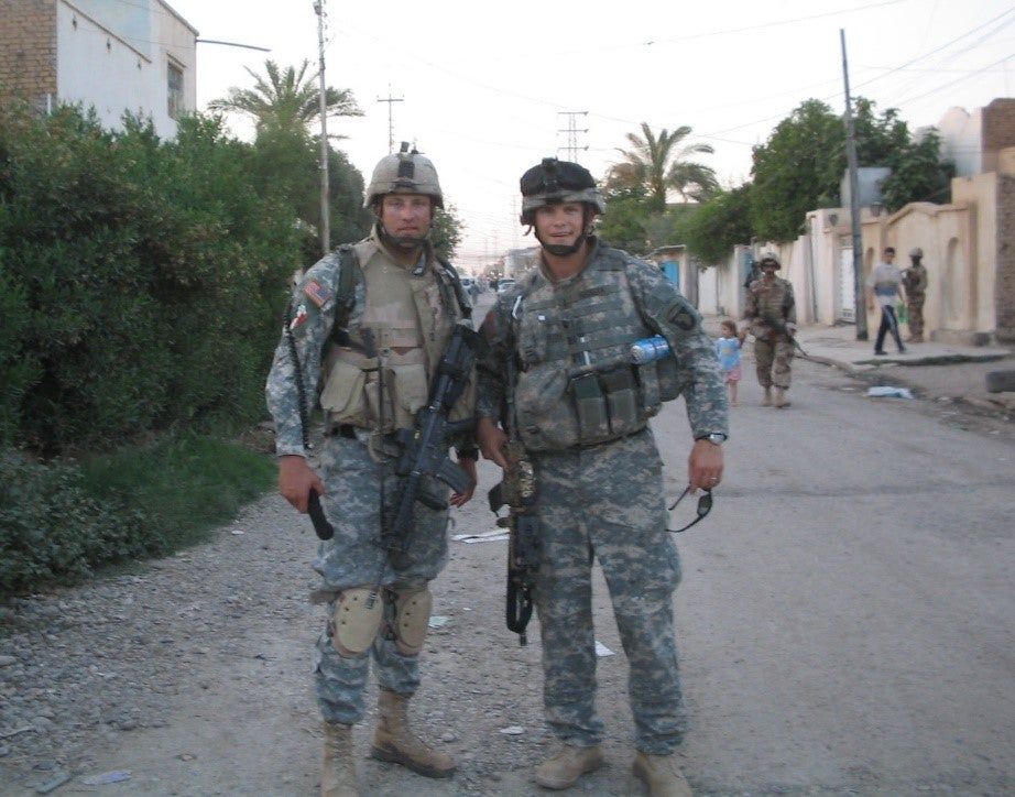 Hegseth poses with a fellow soldier in uniform.