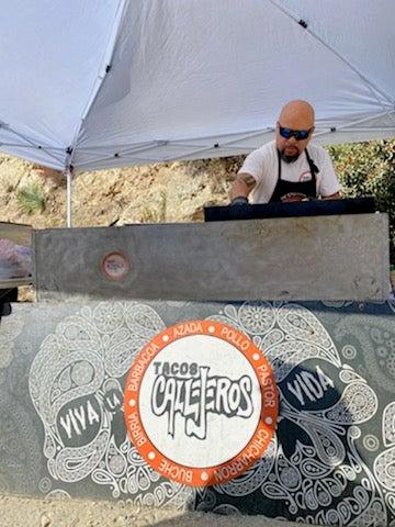 Cortes behind a Tacos Callejeros grill.