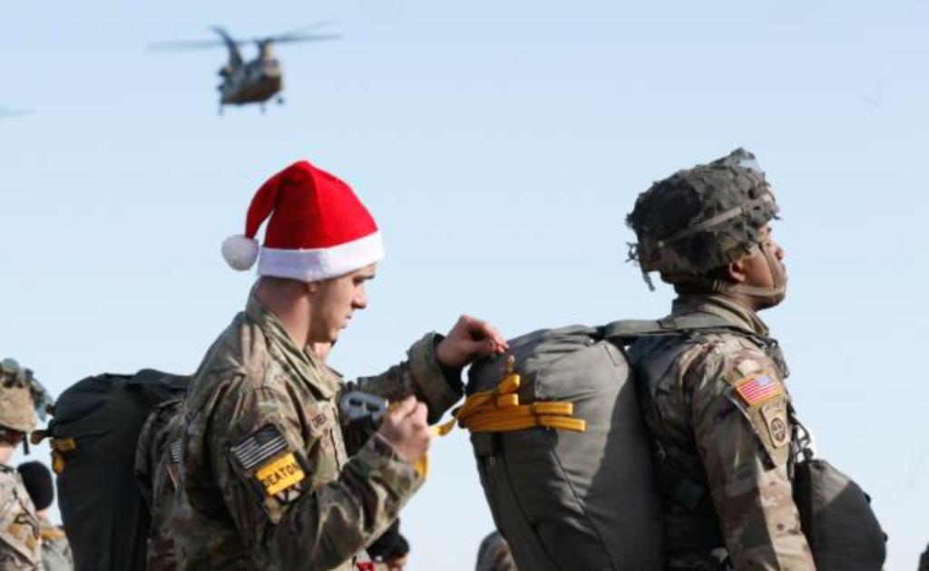 a paratrooper loads presents in a jumper's bag