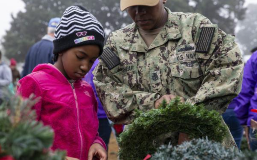 A girl and a Navy service member lay a wreath during Wreaths Across America