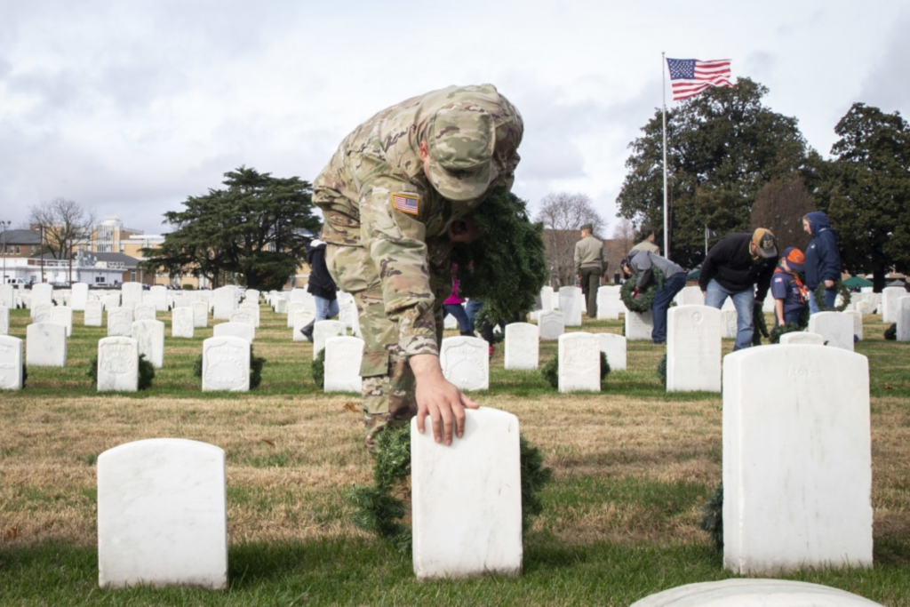A soldier pays his respects at a cemetery