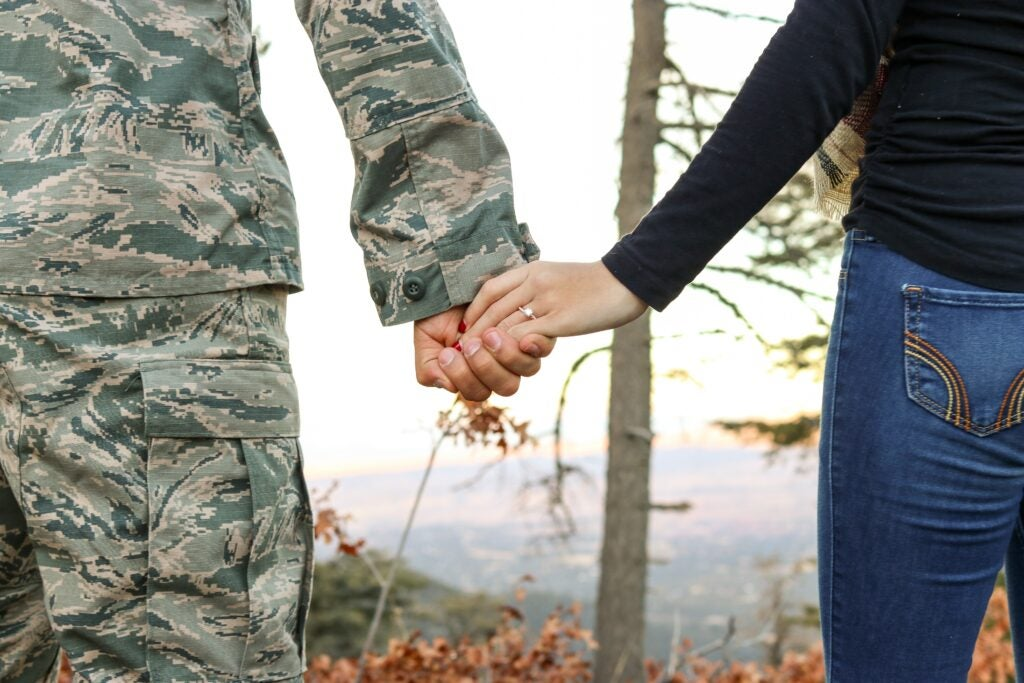 man in uniform holding wife's hand