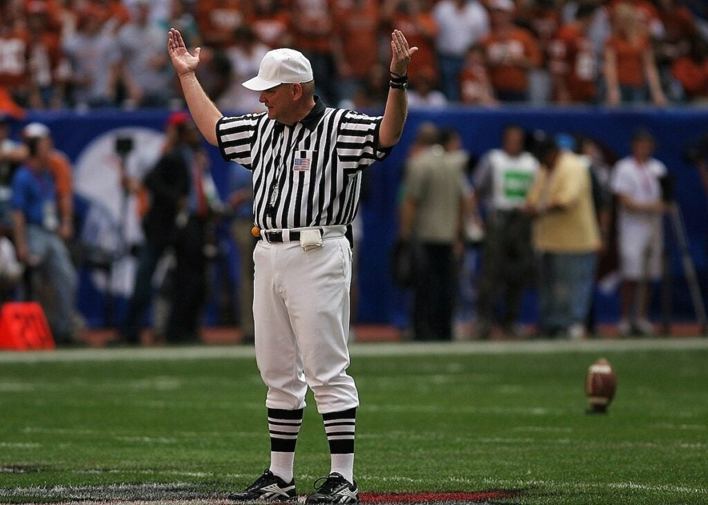 An NFL referee signaling the start of a new quarter. Refs no longer use pistols.