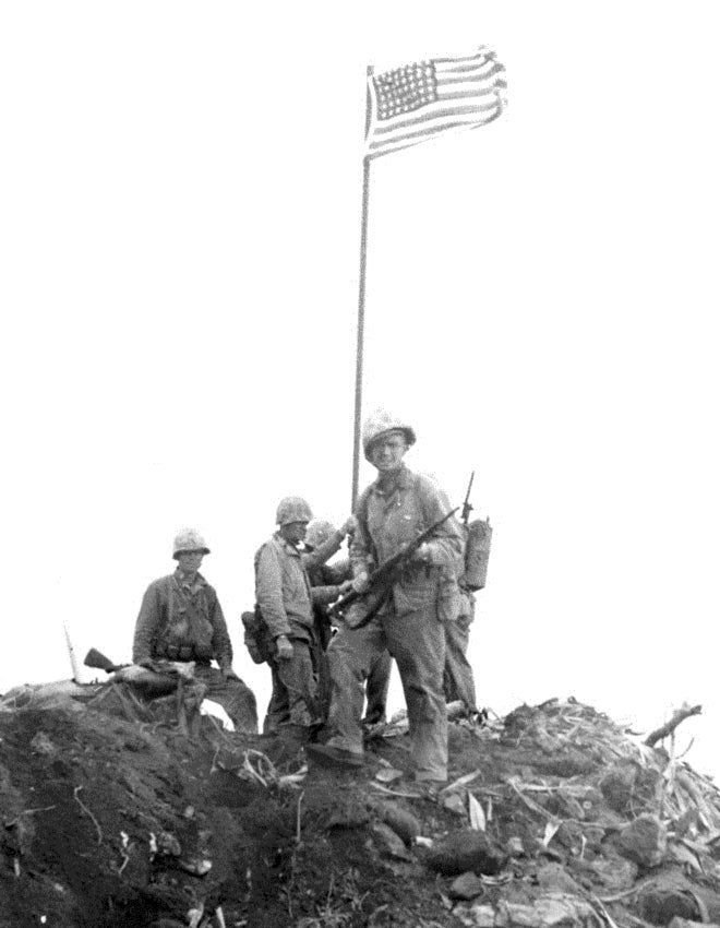 """Detail of a photograph of the first flag-raising on Iwo Jima, showing Ernest Ivy Thomas Jr. in the foreground, facing the viewer. The subject of the photograph is identified in the article """"Another View of the Iwo Flag Raisings"""" by Robert L. Sherrod, appearing in Fortitudine, Vol. X No. 3, Winter 1980–1981"""