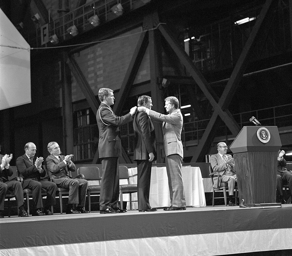 Astronaut Neil Armstrong received the first Congressional Space Medal of Honor from President Jimmy Carter, assisted by Captain Robert Peterson.