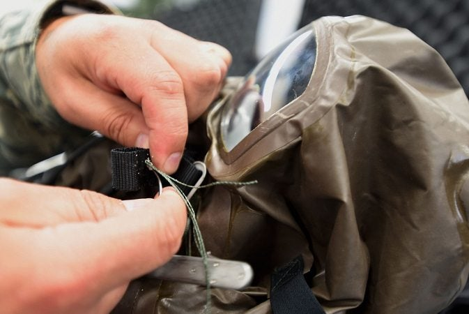 A soldier repairs clothing with a sewing kit, number 2 on our list of useful gear.