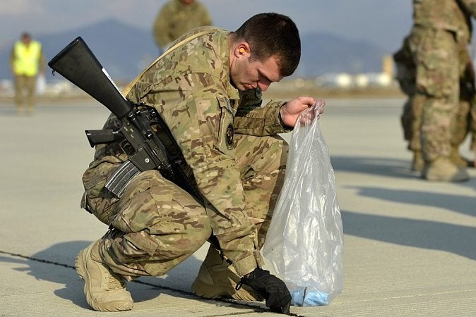 A soldier picks up FOD in a trash bag. Extra water-proofing bags are useful gear.