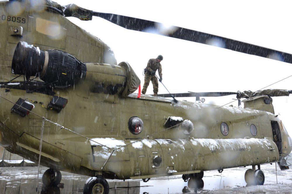 Cold soldier clearing snow off a Chinook