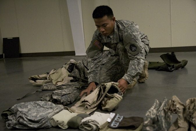 A soldier packs clothes for an upcoming mission. Extra layers are #1 on our list of useful gear.