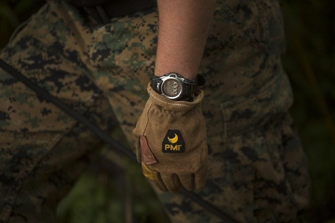 A marine displays a wristwatch. A watch is critical to the useful gear list.