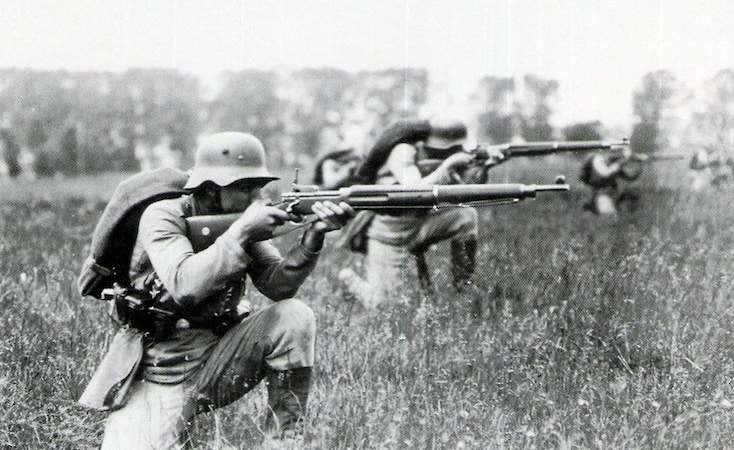 Soldiers crouch in a field, using a precursor weapon to the M16