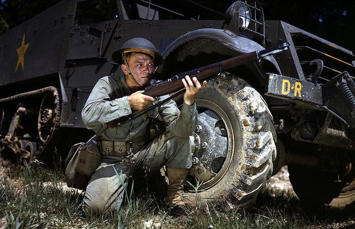 A soldier crouches with an M1 Garand, a precursor to the M16