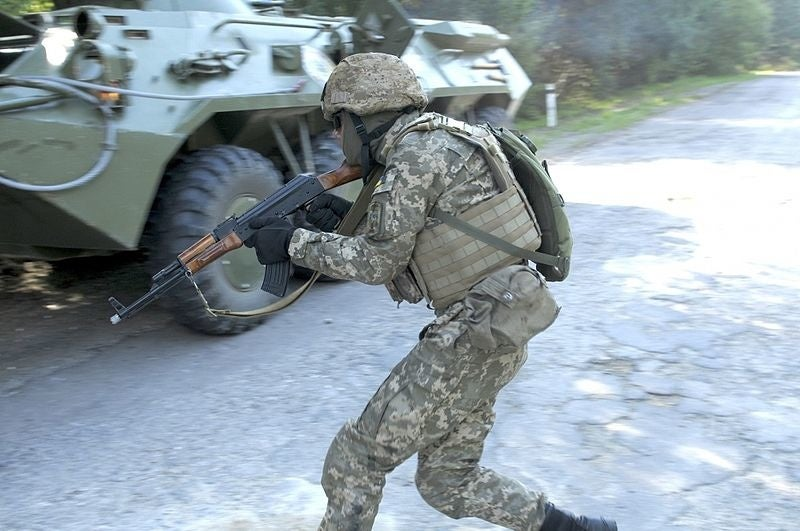 A Ukrainian soldier holding a weapon moves for cover during a training exercise