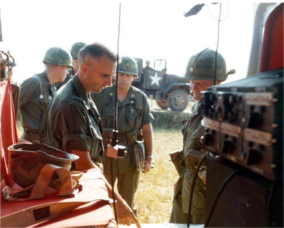 A senior officer is briefed on the progress of Operation Harrison by a commander in the field.  (US Army)