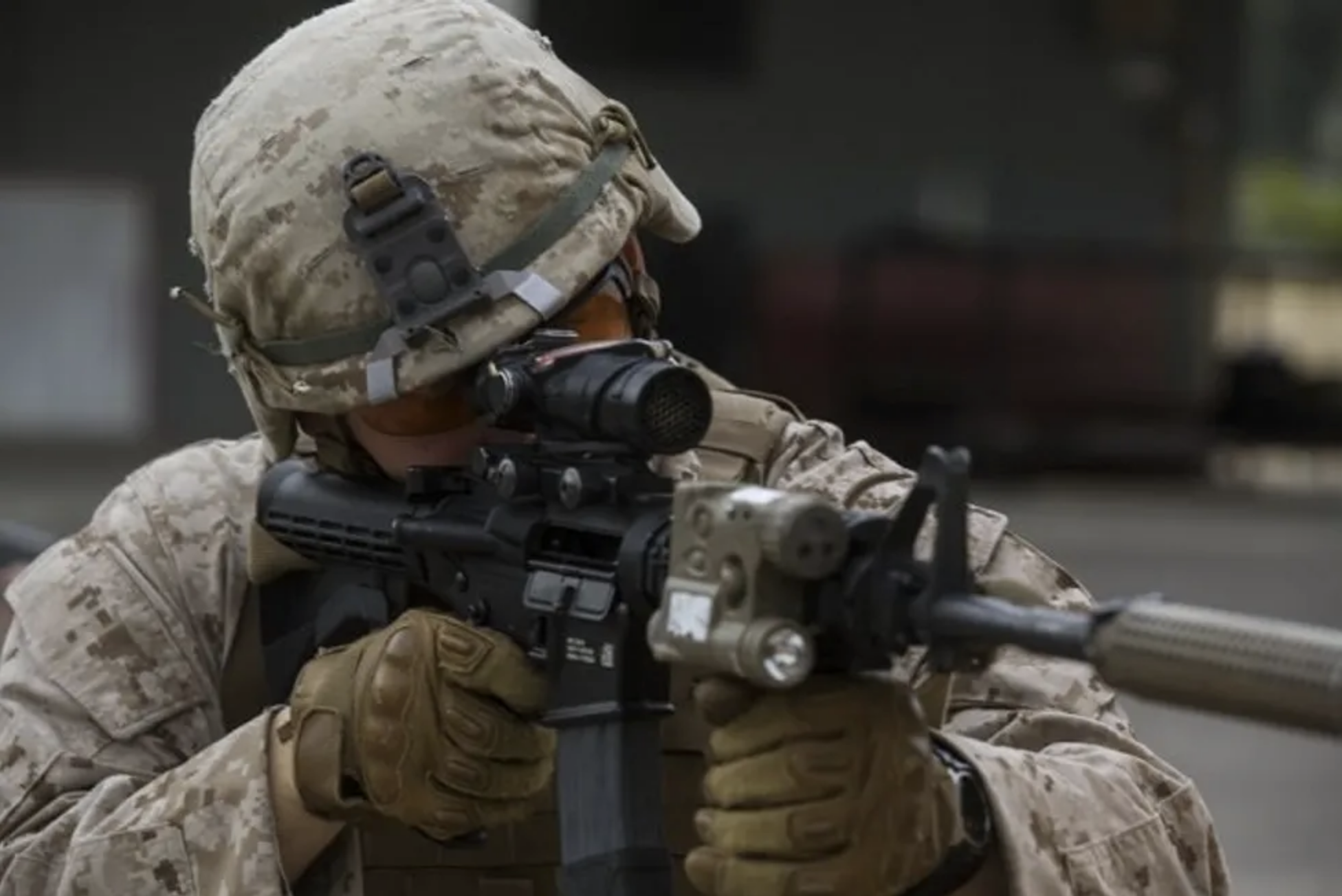 A service member aims a firearm with a suppressor.